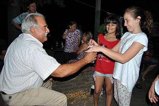 Giachetto abriendo una botella de agua a una niña que se lo pidió en la Plaza Carlos Gardel.