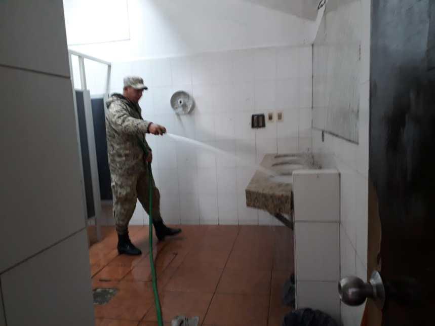 Un soldado realiza una limpieza en la terminal de ómnibus de Florida ante el desabastecimiento de agua potable.